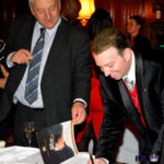 Thomas signing a copy of Crown and Crown and Country Magazine